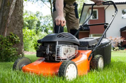 man starting lawnmower out in his yard